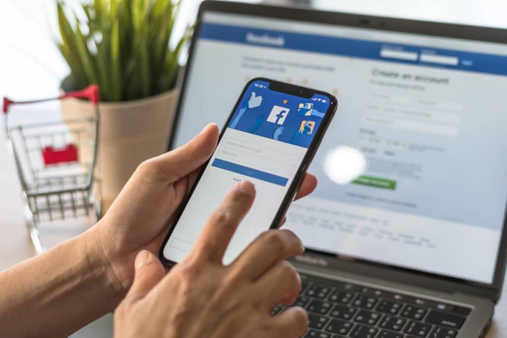 Ein Handy vor einem Laptop auf dem der Facebook Login gezeigt wird.